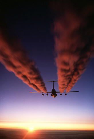 A plane flying at sunset, its contrails colored pink